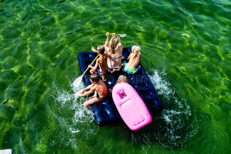 GMUNDEN, ÖSTERREICH, - 3. AUGUST 2018: Glückliche Familie mit Kindern schwimmt und hat Spaß im Meer auf einer aufblasbaren Matrat lizenzfreie stockfotos