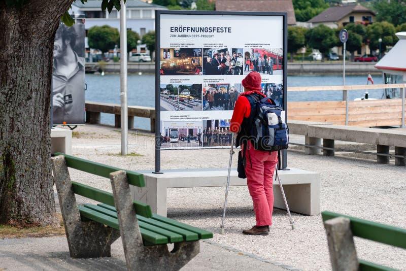 GMUNDEN ÖSTERRIKE, - AUGUSTI 03, 2018: En kvinna med kryckor och en ryggsäck stoppar på affischtavlan och läser royaltyfri foto