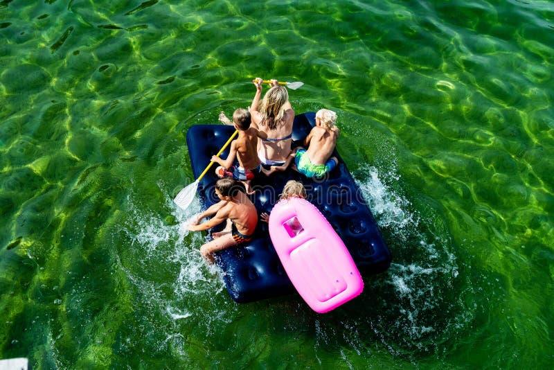 GMUNDEN, AUSTRIA, - 3 DE AGOSTO DE 2018: La familia feliz con los niños está nadando y se está divirtiendo en el mar en un colchó fotos de archivo libres de regalías