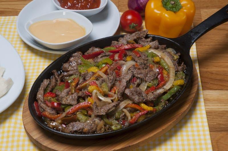 Gnälla fajitas med färgrika spanska peppar i panna och såser royaltyfri foto