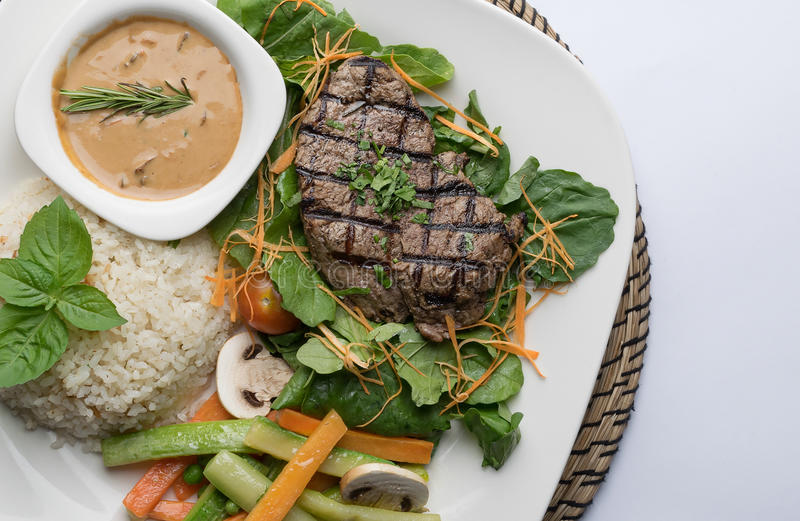 Gnälla filetbiff som tjänas som med ris, grönsaker och champinjonen fotografering för bildbyråer