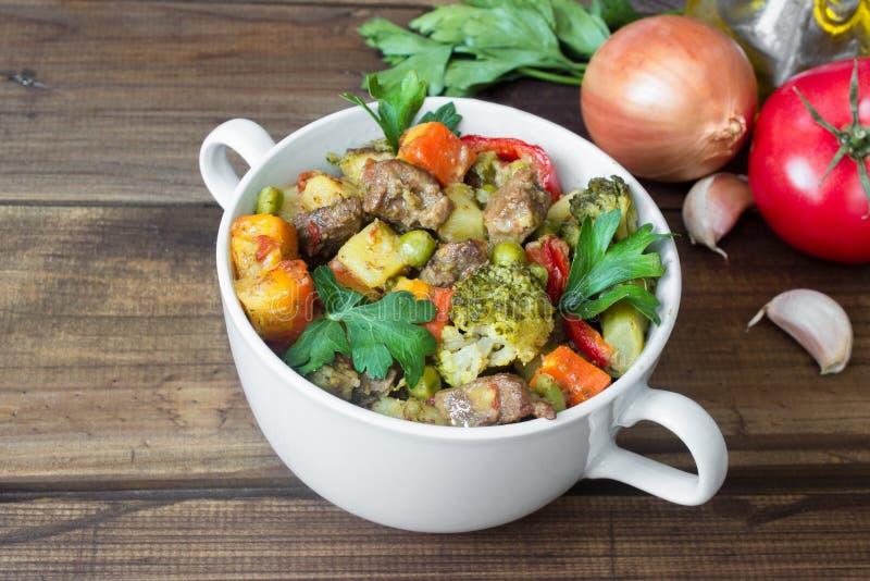 Gnälla kött som låtas småkoka med grönsaker i keramisk kruka med ingredienser på träbakgrund royaltyfri fotografi
