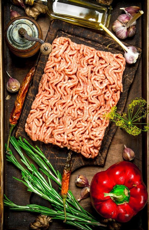 Gnälla köttfärs med kryddor och örter på ett gammalt magasin arkivbild