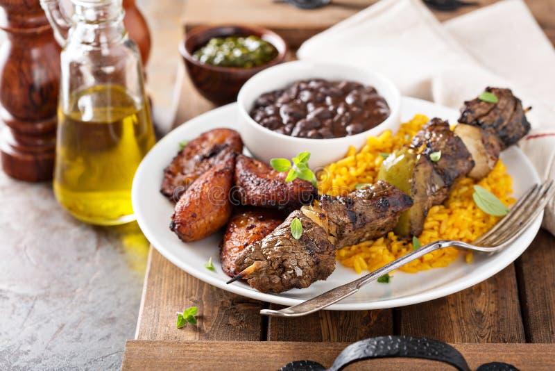 Gnälla kebaben med ris, bönor och stekte pisang arkivbilder