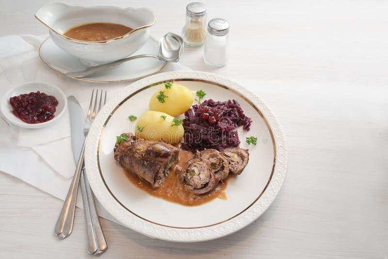 Gnälla rouladen med röd kål, potatisar och sås, tyskt kött r royaltyfri foto