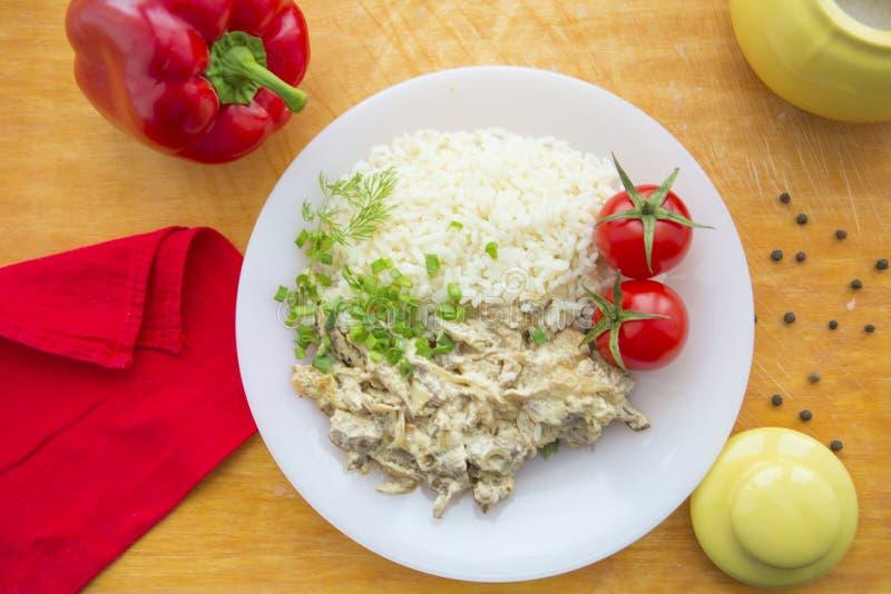 Gnälla stroganoff- och risnärbilden på en platta på tabellen fotografering för bildbyråer