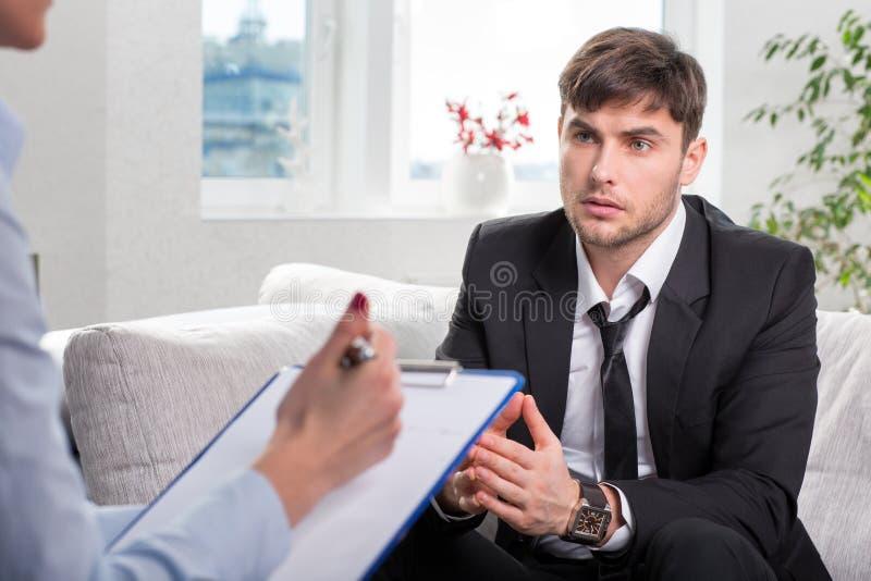 Gnębiony mężczyzna opowiada z psychologiem fotografia royalty free