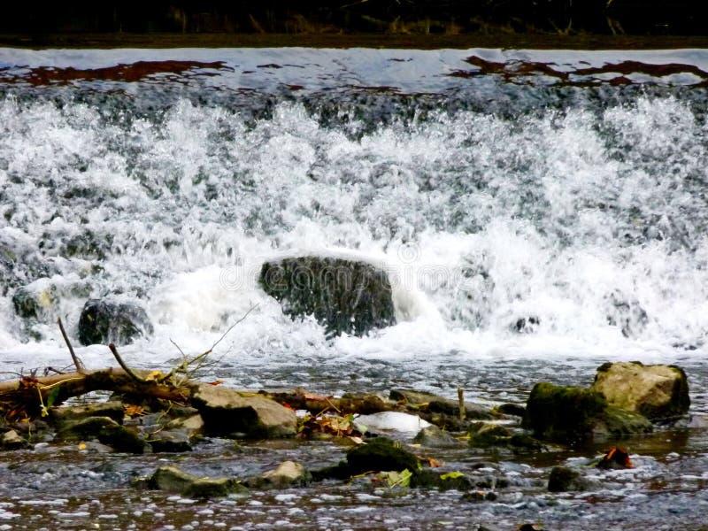 Gnanie siklawa z skałami i skałami przed nim zdjęcie stock