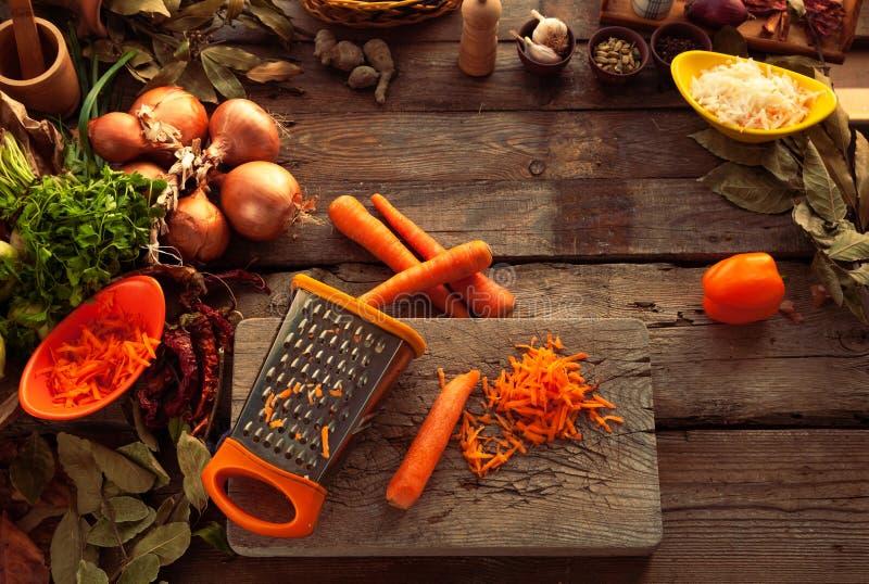 Gnid morötter på ett rivjärn arkivfoto
