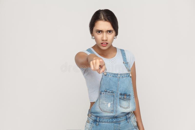 Gniewna łacińska kobieta patrzeje kamerę i poi z drelichowymi kombinezonami zdjęcie stock