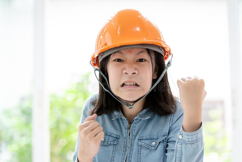 Gniewna azjatykcia małej dziewczynki ręka z pięść gestem z zbawczym hełmem lub ciężkim kapeluszem, zbliżenia śliczny dziecko port zdjęcie stock