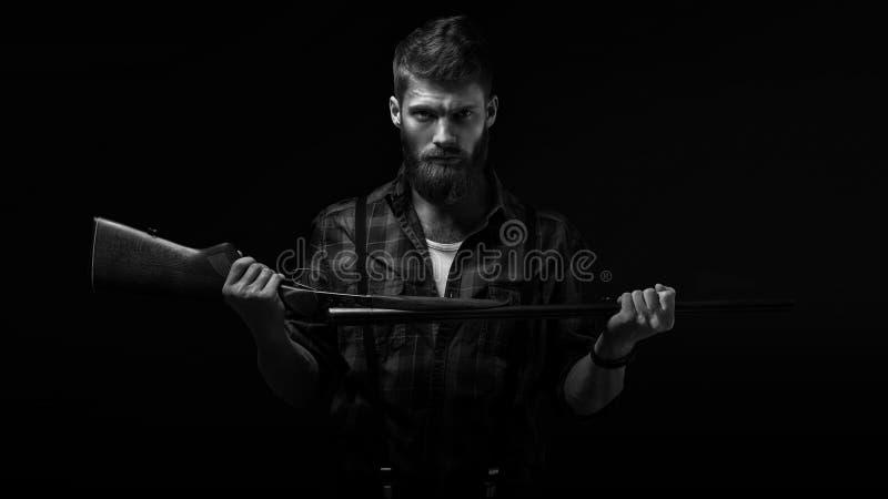 Gniewna brodata mężczyzna mienia flinta fotografia stock