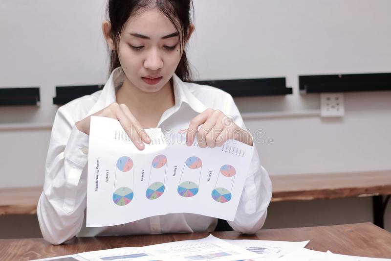 Gniewna dokuczająca Azjatycka biznesowa kobieta drzeje dokumenty tapetuje na biurku w miejscu pracy zdjęcia stock