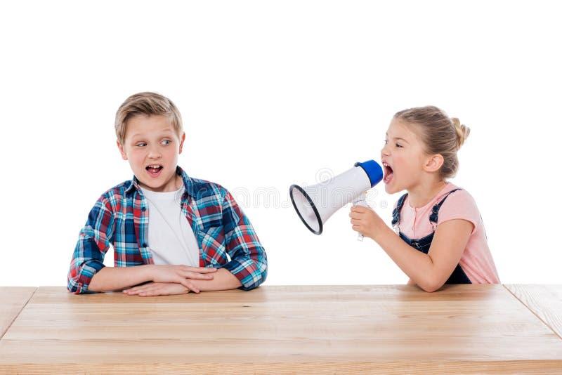 Gniewna dziewczyna wrzeszczy na jej zmieszanym bracie z megafonem fotografia stock