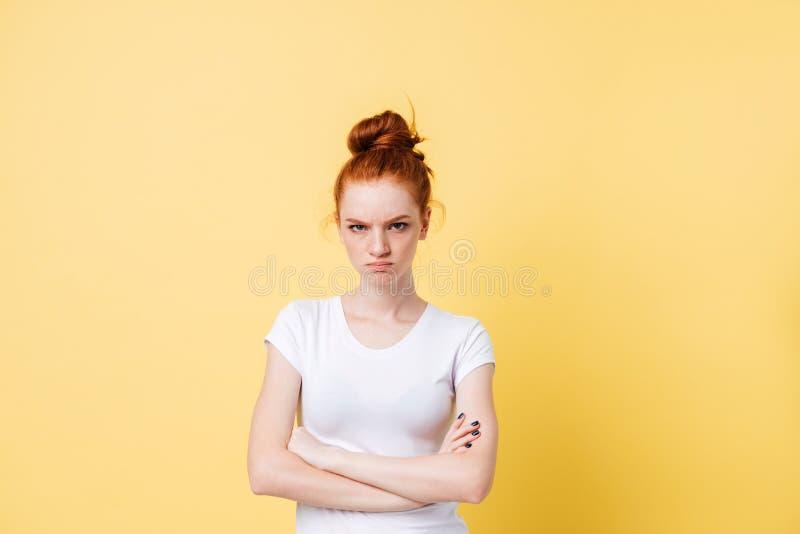 Gniewna imbirowa kobieta pozuje z krzyżować rękami fotografia royalty free