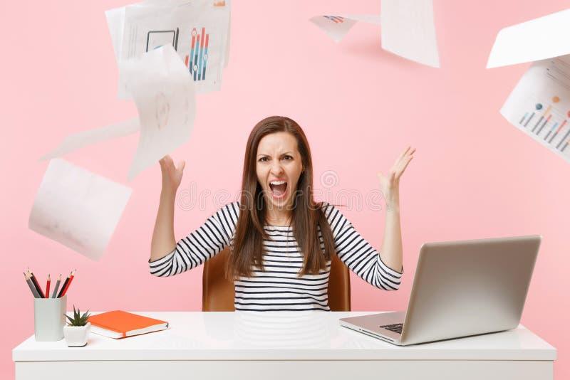 Gniewna kobieta ma problemy krzyczy rzucać w górę papierowych dokumentów podczas gdy pracujący na projekcie, siedzi przy biurem z obrazy stock