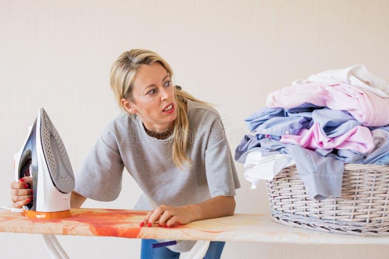 Gniewna kobieta patrzeje stos odziewa przy prasowania biurkiem fotografia stock