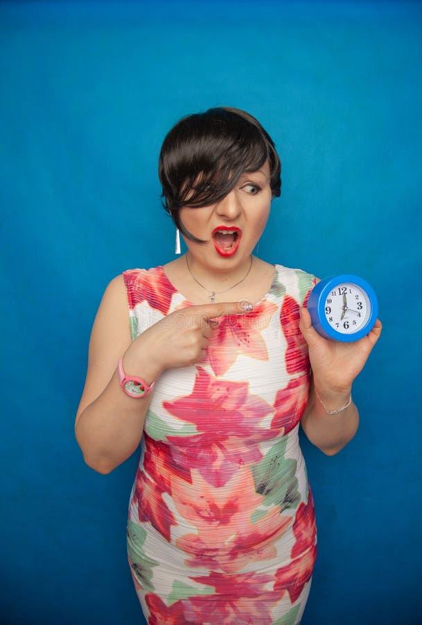 Gniewna krzycząca nieszczęśliwa dziewczyna trzyma round budzika na błękitnym pracownianym tle zdjęcia stock