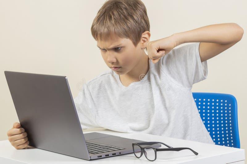 Gniewna młoda chłopiec chce uderzać laptop zdjęcie royalty free
