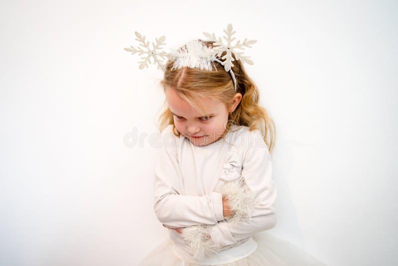 Gniewna młoda dziewczyna w biel sukni przed biel ścianą zdjęcia royalty free
