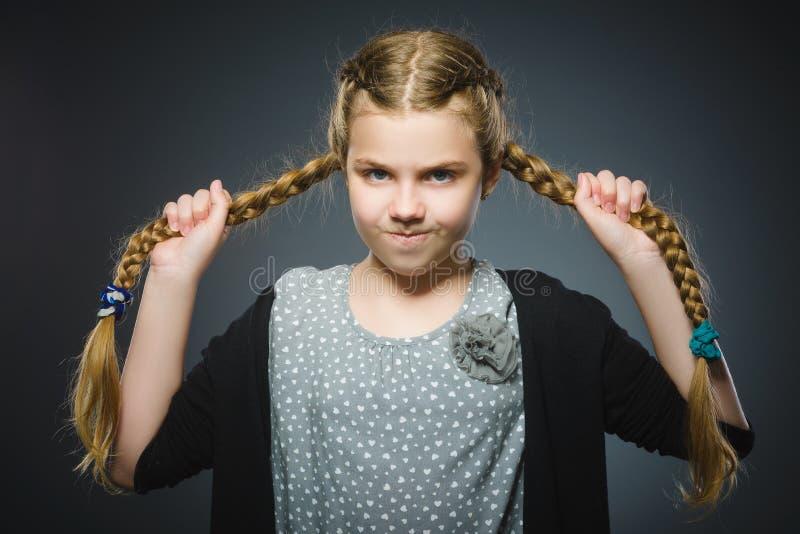 Gniewna mała dziewczynka odizolowywająca na szarym tle obraz stock