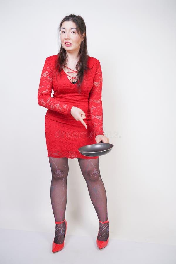 Gniewna negatywna kobieta z cia?a pyzatymi stojakami w czerwieni sukni, chwytach i czarna rynienka na bia?ym pracownianym tle dzi zdjęcie royalty free