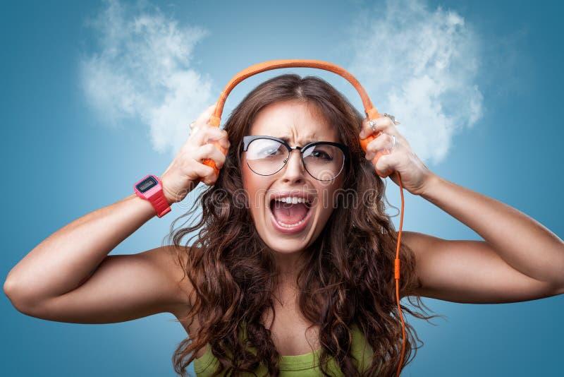 Gniewna nerwowa dziewczyna słucha muzyka w hełmofonach zdjęcie royalty free