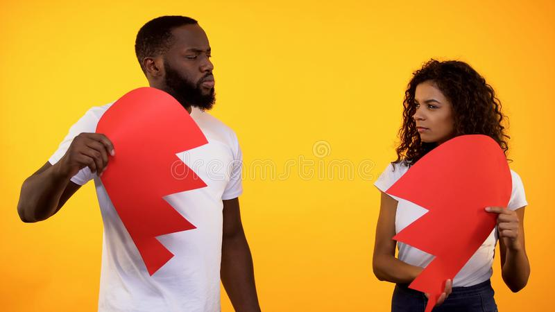 Gniewna para trzyma dwa części papierowy serce, rozbicia związek, kryzys fotografia royalty free
