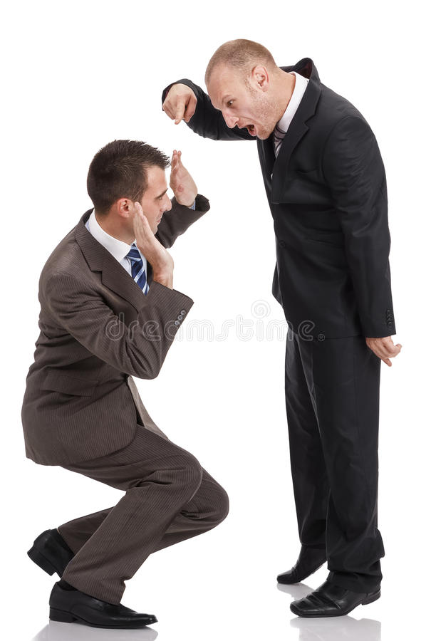 Gniewna pracodawca krzyczy i wskazuje przy skulonym pracownikiem obrazy stock