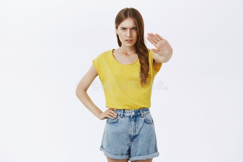 Gniewna przyglądająca ufna młoda nikła dziewczyny ciągnięcia palma w kierunku kamery w żadny, przerwa gest marszczy brwi patrzeć  zdjęcie stock