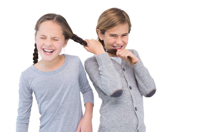 Gniewnego młodego chłopiec ciągnięcia siostrzany włosy w walce fotografia royalty free