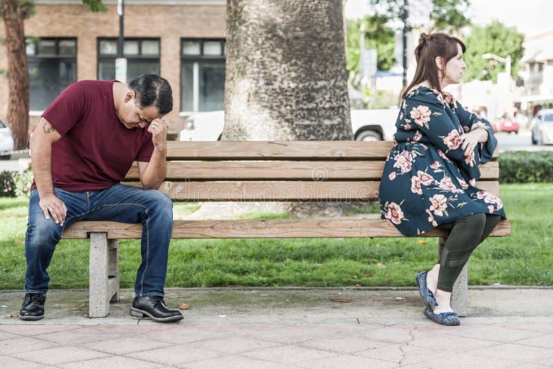 Gniewnej Mieszanej Biegowej pary Siedzący obszycie Zdala od Each Inny na Parkowej ławce zdjęcie royalty free