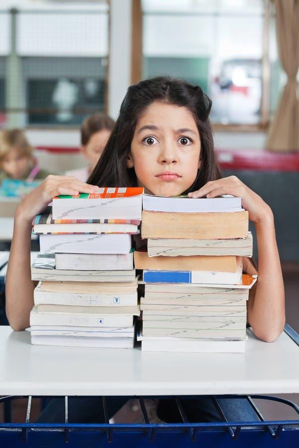 Gniewnej uczennicy Odpoczynkowy podbródek Na książkach obraz stock