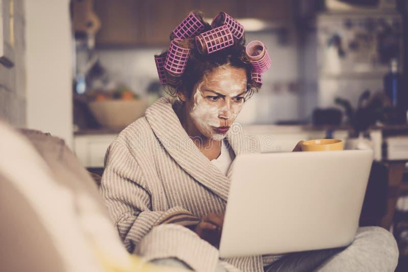 Gniewni i piękni młodzi ludzie wiek średni caucasian kobiety z wellness śmietanki maską na twarzy - patrzejący sieć dla domu robi obrazy royalty free