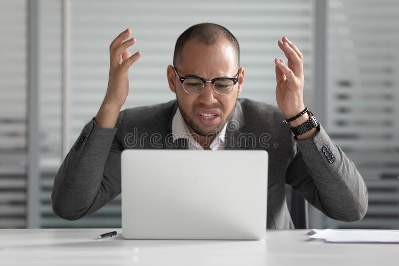 Gniewny afrykański biznesowy mężczyzna używa laptop szalenie o komputerowym problemu obrazy royalty free