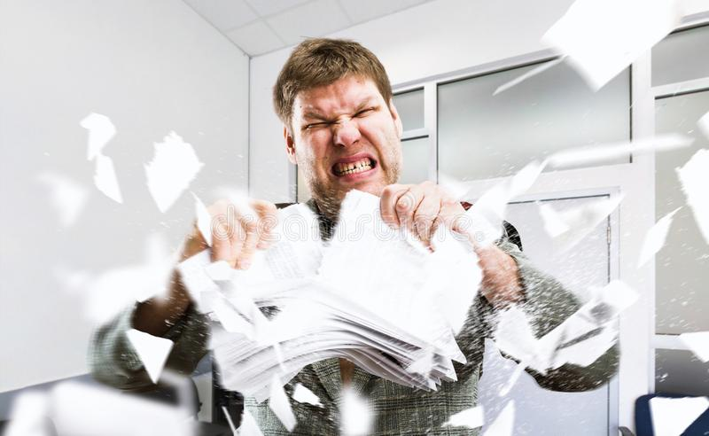 Gniewny biznesmen drzeje sterty papier zdjęcie royalty free
