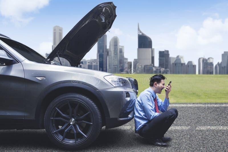 Gniewny biznesmen krzyczy na telefonie przed awaria samochodem fotografia stock