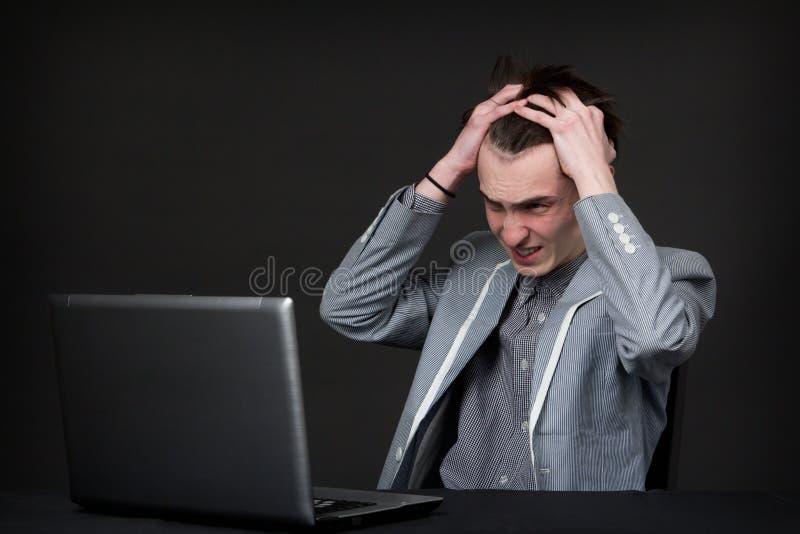 Gniewny caucasian faceta obsiadanie przed komputerem zdjęcie stock