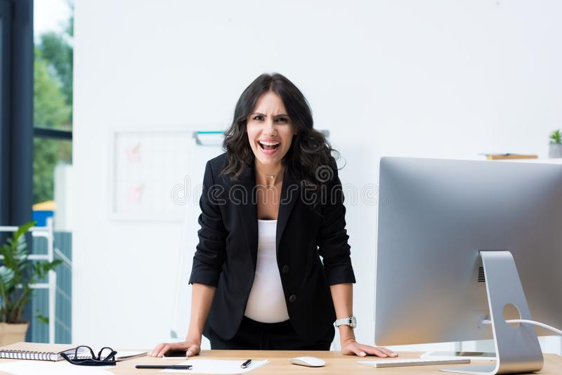 gniewny ciężarny bizneswoman krzyczy podczas gdy patrzejący kamerę obrazy stock