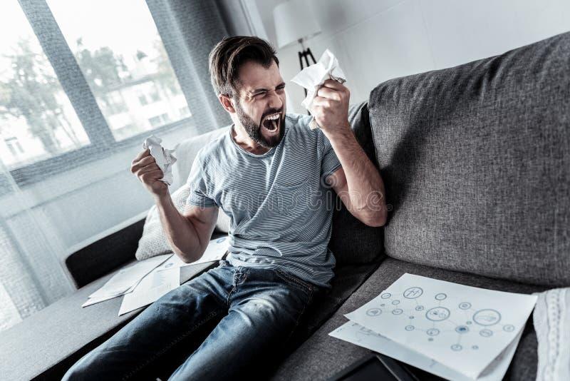 Gniewny emocjonalny mężczyzna miętoszenia papier zdjęcia royalty free