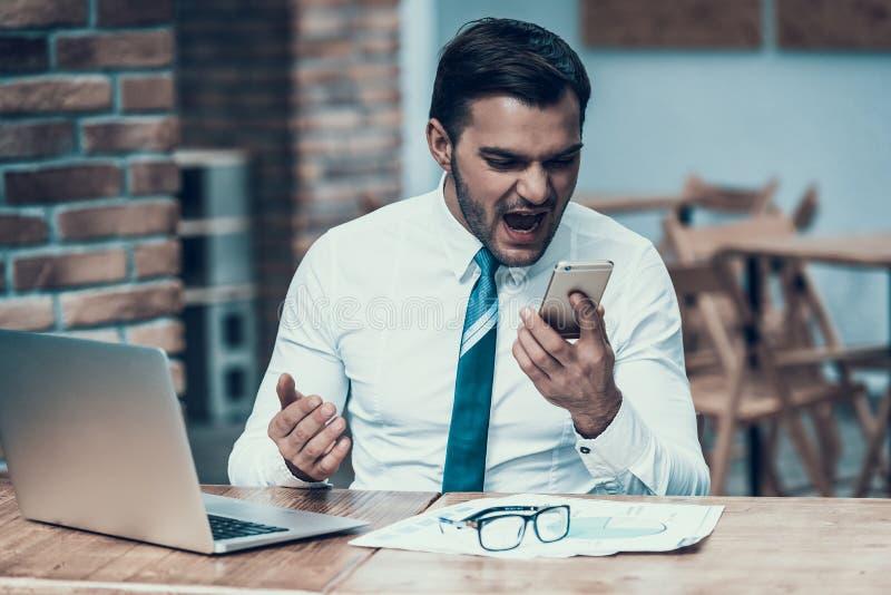 Gniewny Indiański biznesmen krzyczy przy telefonem w biurze fotografia stock