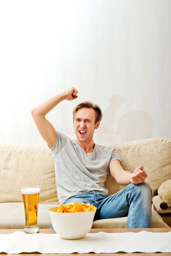 Gniewny mężczyzna krzyczy podczas gdy oglądać bawi się na tv zdjęcia stock