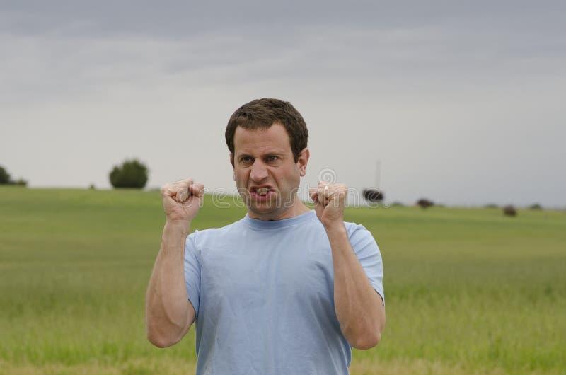 Gniewny mężczyzna outdoors z zaciskać pięściami zdjęcia stock