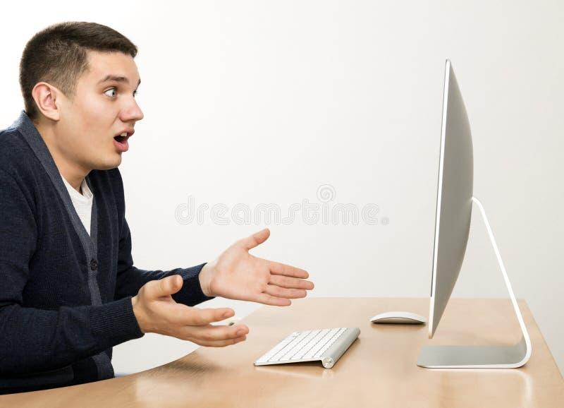 Gniewny mężczyzna wrzeszczy na ekranie komputerowym obraz royalty free