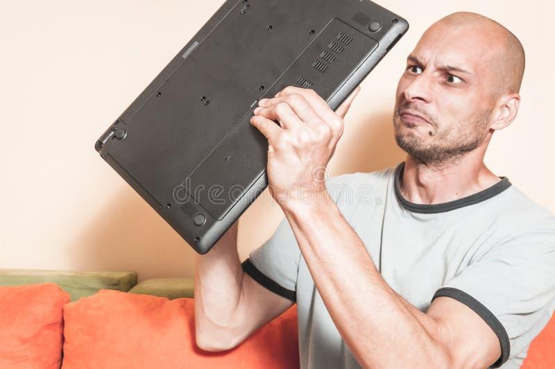 Gniewny mężczyzna wyszukuje internet chce łamać jego laptop po środku jego po tym jak systemu trzaska puszek, selekcyjna ostrość obraz stock