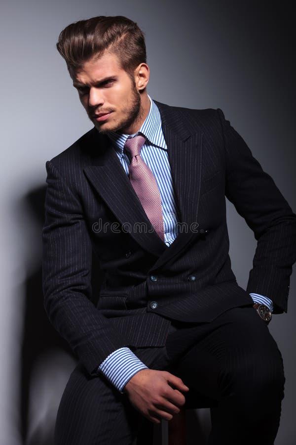 Gniewny młody biznesowy mężczyzna w klasycznym kostiumu i krawata obsiadaniu zdjęcie royalty free