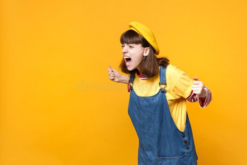 Gniewny podrażniony dziewczyna nastolatek w francuskim berecie, drelichowi sundress patrzeje na boku zaciskać pięści krzyczeć odi obraz royalty free