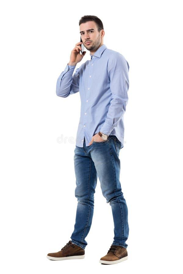 Gniewny poważny biznesmen opowiada na telefonie komórkowym patrzeje kamerę fotografia royalty free