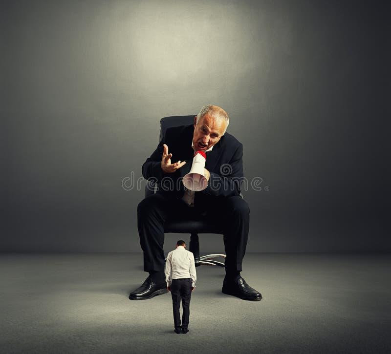 Gniewny szef krzyczy przy małym pracownikiem obrazy stock