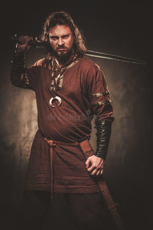 Gniewny Viking z kordzikiem w wojownika tradycyjnych ubraniach, pozuje na ciemnym tle zdjęcie stock
